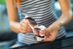Obcieranie okulary przeciwsłoneczni - kobiety słońca czyści szkła z mikro włókna wytarciem zdjęcia stock