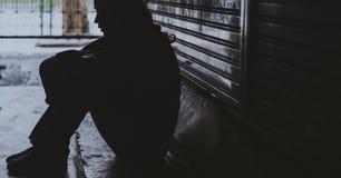 Obdachlose Frau, die auf der Straßen-Seite hoffnungslos sitzt Lizenzfreie Stockfotos