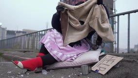 Obdachlose Frau schätzen die Schuhe, die anerkennend auf einer starken roten Socke und Blicken an der Jacke getragen werden stock video footage