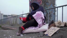 Obdachlose Frau schätzen die Schuhe, die auf einer starken roten Socke getragen werden stock video