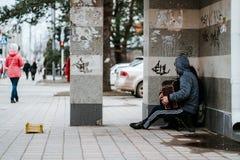 Obdachlose hungrige Musikerbettler mit Akkordeon bittet um Almosen auf Straße nahe der Wand lizenzfreie stockbilder