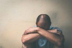 Obdachlose Manndroge und -alkohol gewöhnen das Sitzen allein und deprimiert auf der Straße im Schatten, der besorgt und einsam si Stockbild