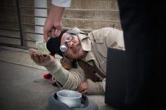 Obdachloser älterer erwachsener Mann, der in der Überführung sitzt und bittet stockfotos