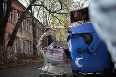 Obdachloser alter Mann mit dem Warenkorb, der nah an Abfalleimer steht Stockfotos