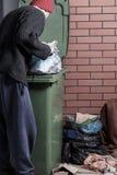 Obdachloser, der nach etwas im Abfall sucht Lizenzfreies Stockfoto
