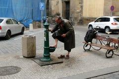 Obdachloser, der seine Füße auf der Straße wäscht Stockbild