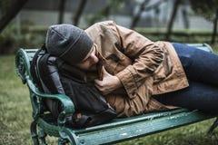 Obdachloser erwachsener Mann, der auf Bank im Park schläft stockfotos