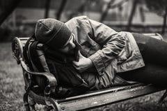 Obdachloser erwachsener Mann, der auf Bank im Park schläft lizenzfreie stockfotos