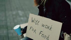 Obdachloser junger Mann bitten um das Geld, das Schale rüttelt, um die Aufmerksamkeitsleute zu zahlen, die nahe Bettler am Stadtb lizenzfreies stockfoto