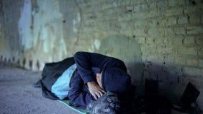 Obdachloser junger Mann, der auf Straße, gleichgültige egoistische Gesellschaft, Armut schläft lizenzfreies stockbild