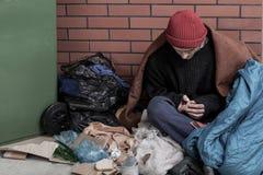 Obdachloser Mann, der auf dem Abfall sitzt Lizenzfreie Stockbilder