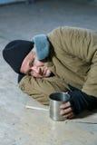 Obdachloser Mann, der auf dem Boden liegt Lizenzfreies Stockfoto