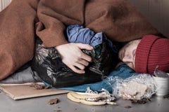 Obdachloser Mann, der auf der Straße liegt lizenzfreies stockfoto