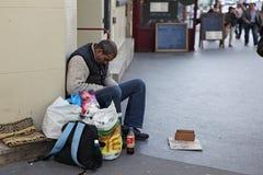 Obdachloser Mann, der auf der Straße und dem Bitten sitzt Stockfotos