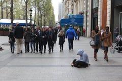 Obdachloser Mann, der auf der Straße und dem Bitten sitzt Stockfotografie