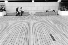 Obdachloser Mann, der auf einer Bank an den Jachthafenbuchtsanden, Singapur schläft lizenzfreie stockfotos
