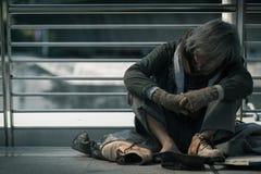 Obdachloser Mann, der auf der Gehwegstraße in der Stadt sitzt Er schläft und benötigt Hilfe von den Güteleuten stockfotos