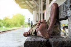 Obdachloser Mann, der an der Bahnstation schläft Lizenzfreies Stockbild