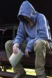 Obdachloser Mann, der eine Flasche sitzt und hält Stockbild