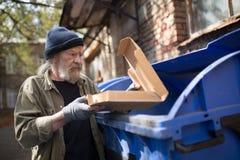 Obdachloser Mann, der nah an dem Abfalleimer, Verpackung von der Pizza halten steht Lizenzfreie Stockfotografie