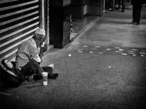 Obdachloser Mann, der sein Abendessen in der Straße nimmt Lizenzfreie Stockbilder