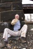 Obdachloser Mann, der unter Eisenbahnbrücke trinkt Stockfotos