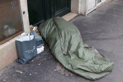 Obdachloser Mann kräuselte sich oben unter einer Plastikplane Stockfoto