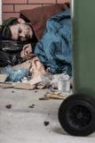 Obdachloser Mann liegt mit Abfall Stockfotos