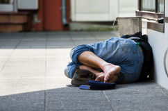 Obdachloser Mann schläft auf der Straße, im Schatten Stockfotografie