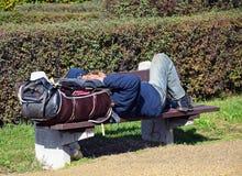 Obdachloser Mann schläft auf einer Bank Lizenzfreie Stockfotos