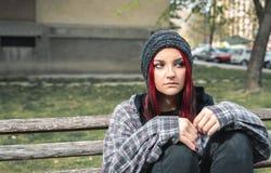 Obdachloses Mädchen, junges schönes rotes Haarmädchen, das allein draußen auf der Holzbank mit dem Hut- und Hemdgefühl besor stockfotografie