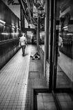 Obdachloses Schlafen aus den Grund und ein touristisches Gehen Stockfotos