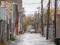Obdrapana typowa północnoamerykańska mieszkaniowa ulica w jesieni w Montreal, Quebec, podczas deszczowego dnia z samochodami park obraz stock