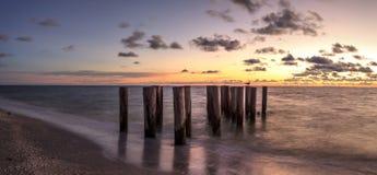 Obdrapane ruiny molo na Portowej Królewskiej plaży przy zmierzchem fotografia stock