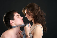 Obedience. Attractive woman pulls naked man by a necktie Stock Images