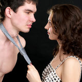 Obedience. Attractive woman pulls naked man by a necktie Royalty Free Stock Photography