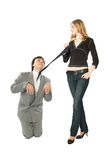 Obedience. A man on all fours and a young woman pulling him by a necktie royalty free stock image