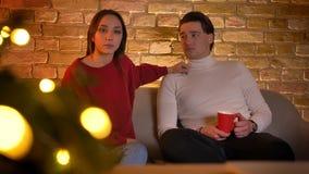 Obejmować caucasian pary obsiadanie na kanapie i attentively oglądać film z filiżanką napój w boże narodzenie atmosferze zbiory