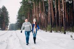 Obejmować pary patrzeje kamerę z uśmiechami w zima parku bereta błękitny nakrętki żakieta ojca zielonej kurtki mum czerwona syna  obraz stock