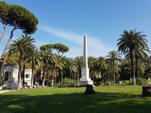 Obelisc i drzewka palmowe w pięknym ogródzie fotografia stock