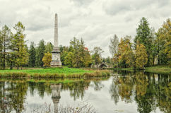 Obelisco di Chesmensky ed il ponte (a dorso d'asino) di Gorbaty in Gatcina Immagine Stock