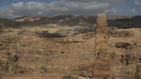 Obelisco en el sitio arqueológico del Petra, y nubes que juegan con el pueblo de Uum Sayhoun imagen de archivo
