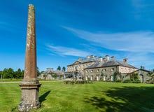 Obelisk and Dumfries House in Cumnock, Scotland, UK. Cumnock, Ayrshire, Scotland, UK - June 18, 2012: Molded stone obelisk in garden of brown stone Dumfries stock photos