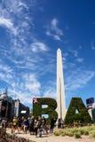 Obelisk und Tourist in der Mitte von Buenos Aires an einem sonnigen Tag Stockfotografie