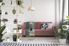 Oben genannte Tabelle der Lampe mit Blumen vor rotem Sofa im weißen Wohnzimmerinnenraum mit Anlagen Reales Foto stockfotos