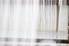 Oben geschlossen vom Webstuhl mit weißem Faden stockfotografie