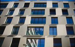 Oben schauen zu einer st?dtischen Fensterfront gegen blauen Himmel stockbild