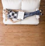 Obenliegende Ansicht der Frau mit Buch auf Couch Lizenzfreie Stockbilder