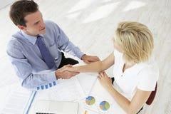 Obenliegende Ansicht der Geschäftsfrau And Businessman Working am Schreibtisch, der zusammen Hände rüttelt Stockbilder