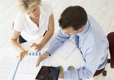 Obenliegende Ansicht der Geschäftsfrau And Businessman Working am Schreibtisch zusammen Lizenzfreie Stockfotos